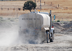 Water Delivery Truck Driving Through Sand